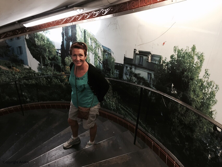 Descending the circular stairs with mural in the Abbesses Metro station.